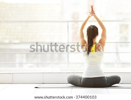 Health concept. Young attractive woman does yoga exercise in the gym  against window - stock photo