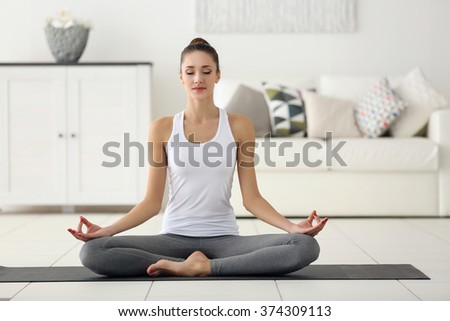 Health concept. Young beautiful woman does yoga exercise in the modern room - stock photo