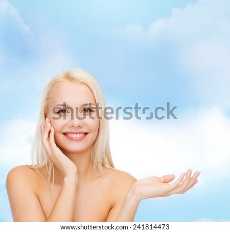 health, cosmetics, advertising and beauty concept - smiling woman holding imaginary lotion jar and applying it - stock photo