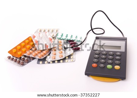 Health cost concept - POS Terminal with a lot of pill tablets (focus on the POS) - stock photo