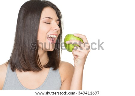 Health feels awesome. Gorgeous happy and healthy young woman with a green apple in her hand isolated on white copyspace on the side - stock photo