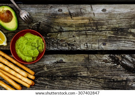 Health food. Guacamole dip with bread sticks over rustic wooden background with space for text. Top view. - stock photo