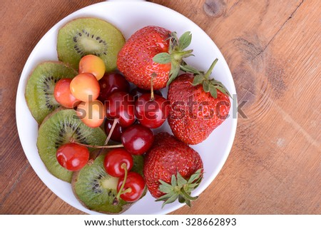 health fruit with cherry, strawberry, kiwi on wooden plate - stock photo