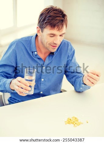 health, healthcare, medicine, medication, drugs, concept - ill man taking his pills at home - stock photo