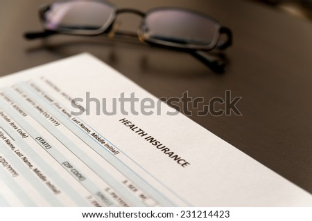 Health insurance form on a table with glasses. selective focus - stock photo