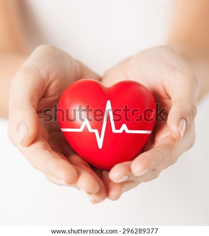 health, medicine and charity concept - closeup of female hands holding red heart with ecg line - stock photo