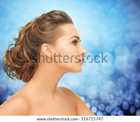 health, people and beauty concept - beautiful young woman face over blue holidays lights background - stock photo