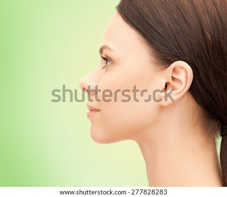 health, people and beauty concept - beautiful young woman face over green background - stock photo