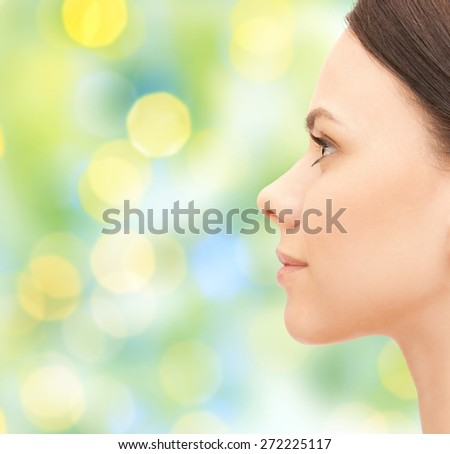 health, people and beauty concept - beautiful young woman face over green holidays lights background - stock photo