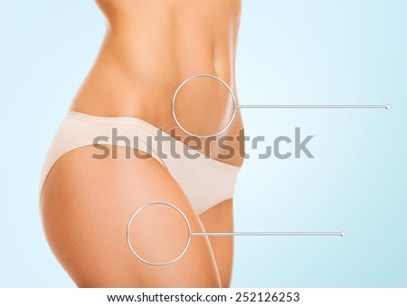health, people and beauty concept - close up of woman hips and torso with magnifier over blue background - stock photo