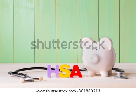 Health Savings Account HSA concept with white  piggy bank, stethoscope wood block letters and green background - stock photo