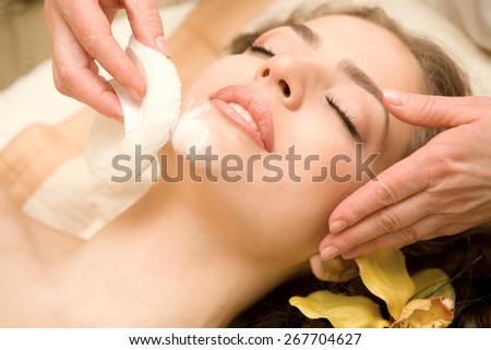 Health spa: close-up of a beautiful relaxing woman having facial massage with a talcom powder - stock photo