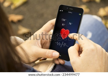 health technology and modern lifestyle concept: young woman using a health app at the park - stock photo