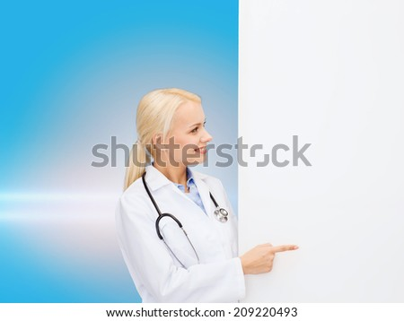 healthcare, advertisement, people and medicine concept - smiling female doctor with stethoscope showing something over blue background - stock photo