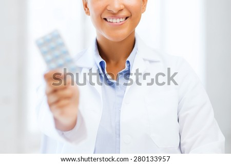 healthcare and medical concept - african doctor with blister packs of pills - stock photo