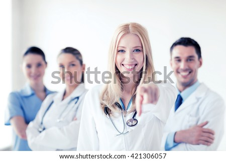 healthcare and medical concept - attractive female doctor in front of medical group - stock photo