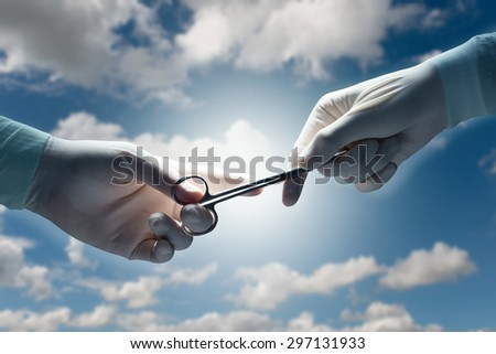 healthcare and medical concept , Close-up of surgeons hands holding surgical scissors and passing surgical equipment on a cloudy sky background. - stock photo