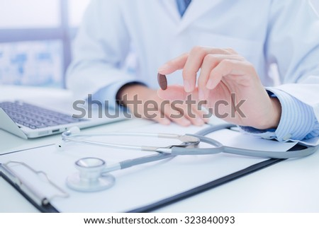 healthcare and medical concept - doctor with pill in hospital - stock photo