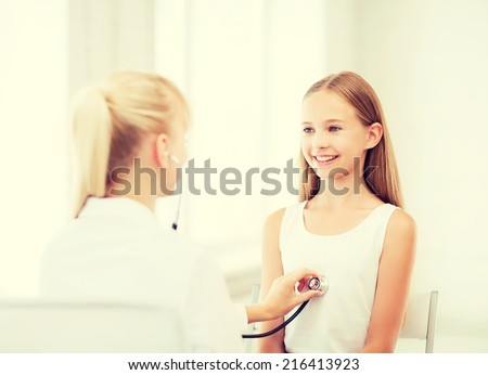 healthcare and medical concept - doctor with stethoscope listening to child chest in hospital - stock photo