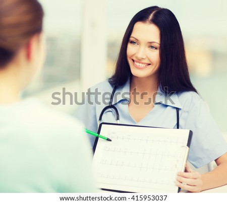 healthcare and medical concept - female doctor or nurse showing cardiogram to patient - stock photo