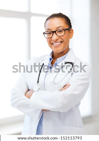 healthcare and medical concept - smiling african female doctor in hospital - stock photo