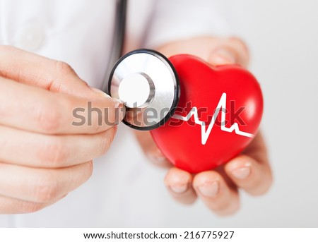 healthcare and medicine concept - close up of male doctor hands holding red heart with ecg line and stethoscope - stock photo