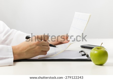 Healthcare and medicine concept - doctor with medical clipboard and green apple analyzing cardiogram - stock photo