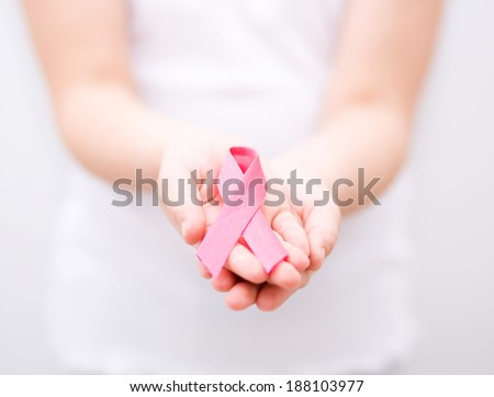 healthcare and medicine concept - girl hands holding pink breast cancer awareness ribbon - stock photo
