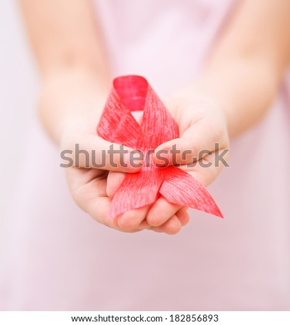 Healthcare and medicine concept - girl hands holding red breast cancer awareness ribbon - stock photo