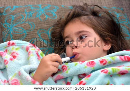 Healthcare and medicine concept - ill girl child with thermometer in mouth. - stock photo