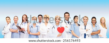 healthcare and medicine concept - smiling doctors and nurses with red heart - stock photo