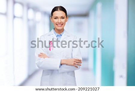 healthcare and medicine concept - smiling female doctor with pink cancer awareness ribbon over hospital background - stock photo