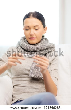 healthcare, home and medicine concept - ill woman with flu at home looking at thermometer - stock photo