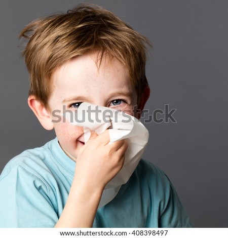 healthcare learning - happy young kid with red hair and freckles enjoying using a tissue after a cold, rhinitis or spring allergies, grey background studio - stock photo