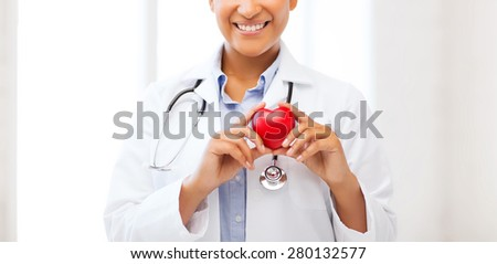 healthcare, medical and cardiology concept - african female doctor with heart - stock photo