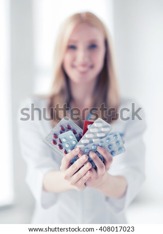 healthcare, medical and pharmacy concept - female doctor with packs of pills - stock photo