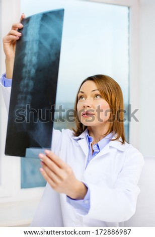 healthcare, medical and radiology concept - concentrated doctor looking at x-ray - stock photo