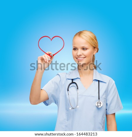 healthcare, medical and technology - young doctor or nurse drawing red heart - stock photo