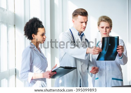Healthcare, medical: Group of multi-ethnic doctors discussing and looking x-ray in a clinic or hospital.  - stock photo