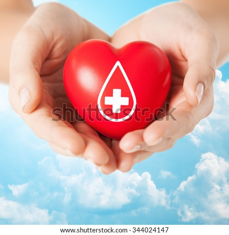 healthcare, medicine and blood donation concept - female hands holding red heart with donor sign over blue sky and clouds background - stock photo