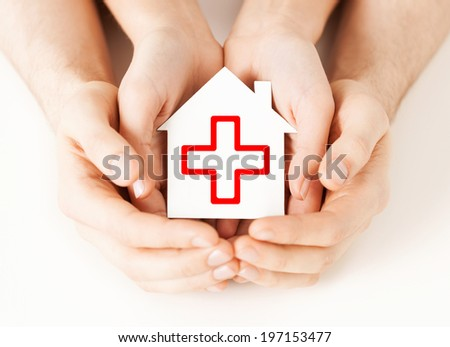 healthcare, medicine and charity concept - male and female hands holding white paper house with red cross sign - stock photo