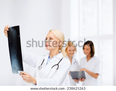 healthcare, medicine and radiology concept - serious female doctor looking at x-ray - stock photo