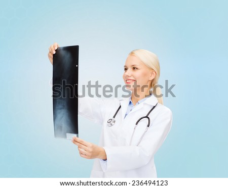healthcare, medicine and radiology concept - smiling female doctor looking at x-ray image over blue background - stock photo