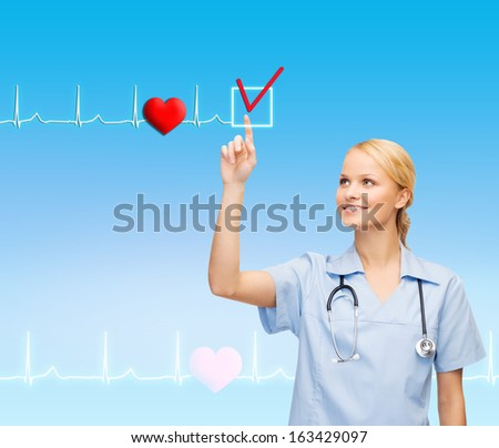 healthcare, medicine and technology concept - smiling young doctor or nurse pointing to something or pressing imaginary button - stock photo