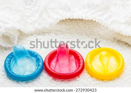 Healthcare medicine, contraception and birth control. Closeup colorful condoms with lace lingerie. - stock photo