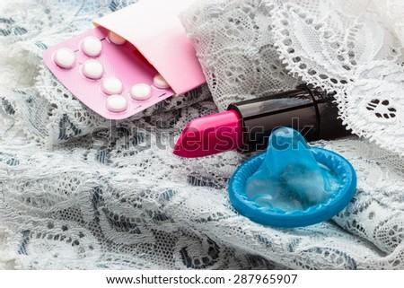 Healthcare medicine, contraception and birth control. Closeup oral contraceptive pills, condom and red lipstick on lace lingerie. - stock photo