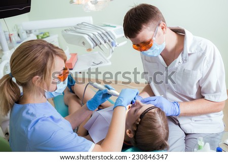 Healthcare, medicine. Young woman with dentist in a dental surgery. - stock photo