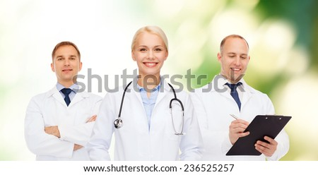 healthcare, people and medicine concept - group of doctors with stethoscopes and clipboard over green background - stock photo