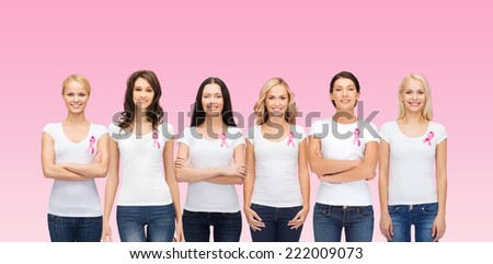 healthcare, people and medicine concept - group of smiling women in blank t-shirts with breast cancer awareness ribbons over pink background - stock photo