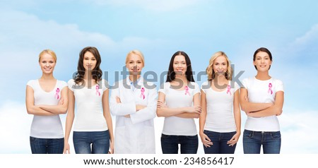 healthcare, people and medicine concept - group of smiling women in blank t-shirts with pink breast cancer awareness ribbons blue sky background - stock photo